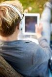 Ciérrese para arriba de adolescente en auriculares con PC de la tableta Imagenes de archivo