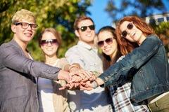 Ciérrese para arriba de amigos adolescentes con las manos en el top Fotos de archivo libres de regalías