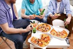 Ciérrese para arriba de amigos con la cerveza y la pizza en casa Imagen de archivo libre de regalías