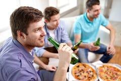 Ciérrese para arriba de amigos con la cerveza y la pizza en casa Fotos de archivo libres de regalías