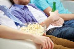 Ciérrese para arriba de amigos con la cerveza y las palomitas en casa Fotos de archivo
