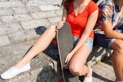 Ciérrese para arriba de amigos con longboard en la calle Fotografía de archivo libre de regalías