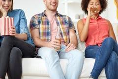 Ciérrese para arriba de amigos con palomitas y cerveza en casa Imagen de archivo