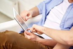 Ciérrese para arriba de amigos con PC de la tableta en casa Foto de archivo