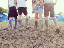 Ciérrese para arriba de amigos en Wellington Boots Walking To Festival foto de archivo