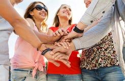 Ciérrese para arriba de amigos felices con las manos en el top Fotografía de archivo