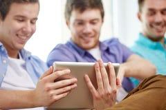Ciérrese para arriba de amigos felices con PC de la tableta en casa Fotos de archivo libres de regalías