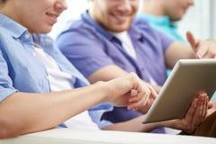 Ciérrese para arriba de amigos felices con PC de la tableta en casa Imágenes de archivo libres de regalías