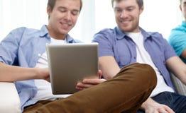 Ciérrese para arriba de amigos felices con PC de la tableta en casa Foto de archivo