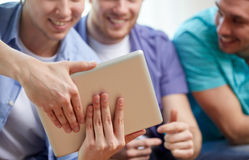 Ciérrese para arriba de amigos felices con PC de la tableta en casa Fotos de archivo