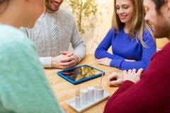 Ciérrese para arriba de amigos felices con PC de la tableta en el café Imágenes de archivo libres de regalías
