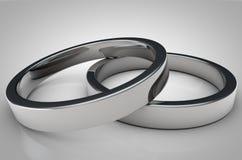 Ciérrese para arriba de 2 anillos de plata del hockey shinny en fondo gris Fotografía de archivo