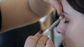 Ciérrese para arriba de aplicar los sombreadores de ojos de la sepia a la tapa del ojo izquierdo de la mujer joven almacen de metraje de vídeo