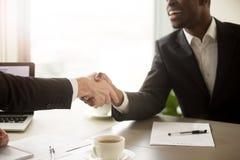 Ciérrese para arriba de apretón de manos entre los socios comerciales blancos y negros Imagen de archivo libre de regalías