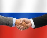 Ciérrese para arriba de apretón de manos sobre la bandera rusa Imagenes de archivo