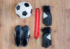 Ciérrese para arriba de balón de fútbol, de botas, de guantes y de la medalla imagenes de archivo