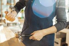 Ciérrese para arriba de barista con el pisón y pistón o portafilter que hace el café express imagenes de archivo