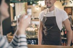 Ciérrese para arriba de barista masculino sonriente en el contador de la barra imagenes de archivo