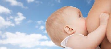 Ciérrese para arriba de bebé de amamantamiento sobre el cielo azul Foto de archivo libre de regalías