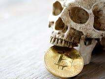 Ciérrese para arriba de bitcoin de oro penetrante del cráneo en la tabla de madera El concepto de inversión y fluctuación del bit fotos de archivo libres de regalías