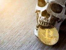 Ciérrese para arriba de bitcoin de oro penetrante del cráneo en la tabla de madera El concepto de inversión y fluctuación del bit imagenes de archivo
