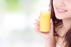Ciérrese para arriba de boca de la mujer con el zumo de naranja Imágenes de archivo libres de regalías
