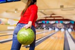 Ciérrese para arriba de bola que lanza de la mujer en club de los bolos Foto de archivo libre de regalías