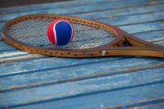Ciérrese para arriba de bola roja y azul en la estafa de tenis de madera Fotos de archivo