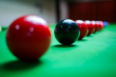 Ciérrese para arriba de bolas rojas y negras en la tabla de billar Fotografía de archivo