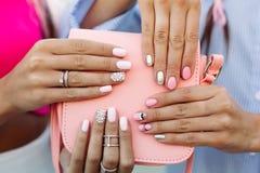 Ciérrese para arriba de bolso con las manos de las muchachas con la manicura sobre ella Imagen de archivo