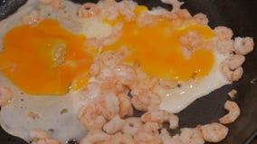 Ciérrese para arriba de camarones fritos con los huevos en un sartén con aceite 4k UHD almacen de metraje de vídeo