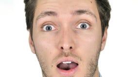 Ciérrese para arriba de cara sorprendida del hombre joven en el fondo blanco almacen de video