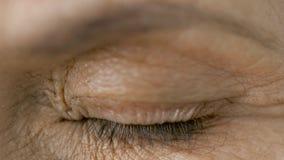 Ciérrese para arriba de centellar el ojo mayor de la mujer almacen de metraje de vídeo