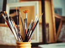 Ciérrese para arriba de cepillos de pintura en el estudio del artista Fotografía de archivo