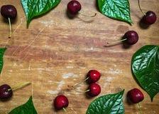 Ciérrese para arriba de cereza roja fresca de la baya y de la hoja verde en fondo de madera Fotografía de archivo