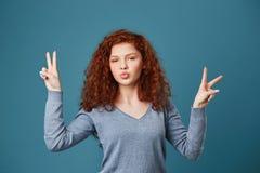 Ciérrese para arriba de chica joven alegre con el pelo y las pecas rojos ondulados con gesto de la paz en ambas manos, haciendo l Imagen de archivo