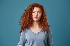 Ciérrese para arriba de chica joven bonita con el pelo y las pecas ondulados del jengibre en la camisa gris que tiene dolor de ca Foto de archivo