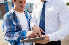 Ciérrese para arriba de constructor y de hombre de negocios con PC de la tableta imagenes de archivo