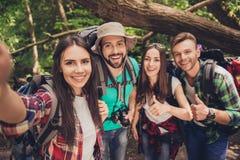 Ciérrese para arriba de cuatro amigos alegres en la madera agradable del verano, abarcamiento, presentando para un tiro del selfi fotos de archivo