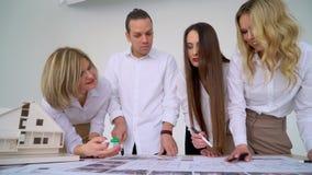 Ciérrese para arriba de cuatro arquitectos que discuten plan junto en el escritorio con los modelos metrajes