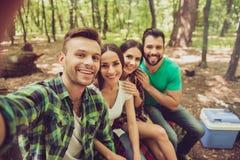 Ciérrese para arriba de cuatro turistas felices de los amigos en la madera agradable de la primavera, Foto de archivo libre de regalías