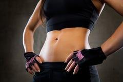 Ciérrese para arriba de cuerpo de la mujer joven en gimnasio Foto de archivo libre de regalías