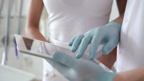 Ciérrese para arriba de dentista con la mujer que usa la tableta con la radiografía de dientes almacen de video