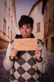 Ciérrese para arriba de desamparados con la descripción de la cartulina de la caridad, en un fondo borroso Foto de archivo libre de regalías