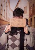 Ciérrese para arriba de desamparados con la descripción de la cartulina del dinero por favor, en un fondo borroso Foto de archivo