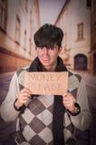 Ciérrese para arriba de desamparados con la descripción de la cartulina del dinero por favor, en un fondo borroso Fotos de archivo libres de regalías