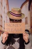 Ciérrese para arriba de desamparados con la descripción de la cartulina del dinero por favor, llevando un sombrero, en un fondo b Imagen de archivo
