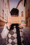 Ciérrese para arriba de desamparados con la descripción de la cartulina del dinero por favor, ocultando el hald de su cara, en un Imagen de archivo