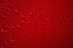 Ciérrese para arriba de descensos del agua en fondo rojo Foto de archivo libre de regalías