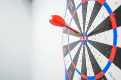 Ciérrese para arriba de diana con las flechas del dardo en el centro Imagen de archivo